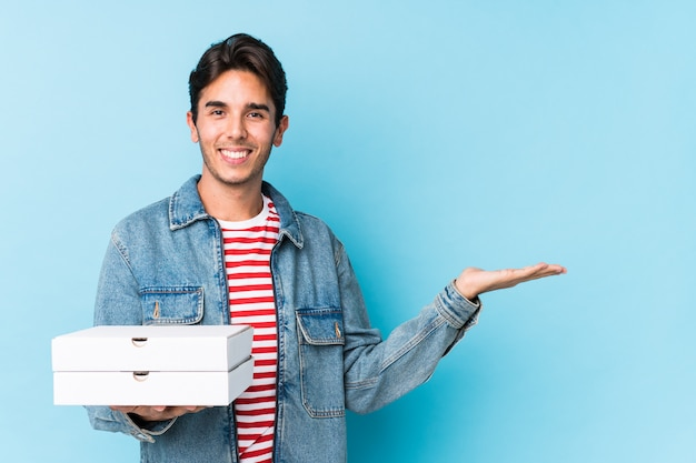 Young caucasian man holding pizzas isolated showing a copy space on a palm and holding another hand on waist.