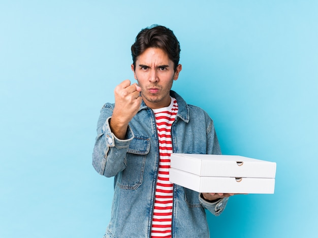 Young caucasian man holding pizzas isolated showing fist to camera, aggressive facial expression.