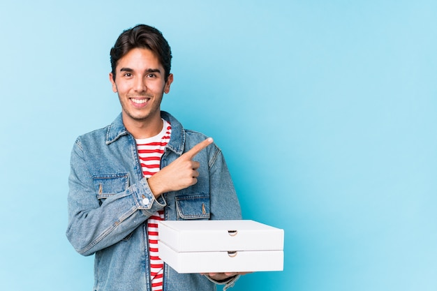 Young caucasian man holding pizzas isolated smiling and pointing aside, showing something at blank space.