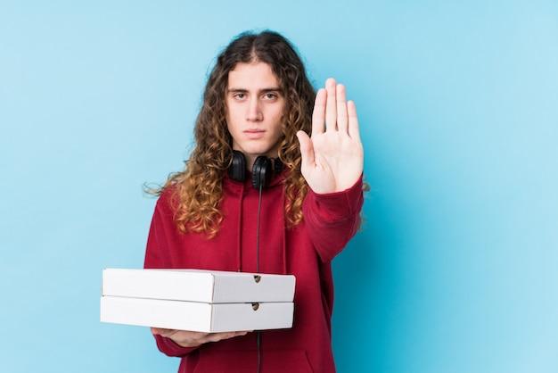 Молодой кавказский человек, держащий пиццу, изолировал стоя с протянутой рукой, показывая знак остановки, предотвращая вас.