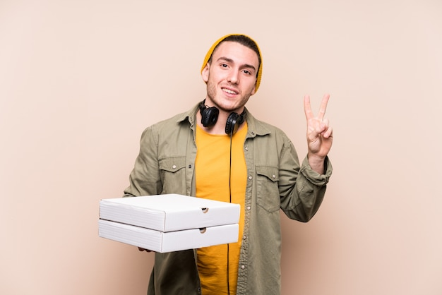 Young caucasian man holding pizzas joyful and carefree showing a peace symbol with fingers.