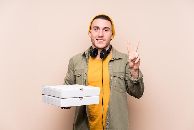 Молодой кавказский человек держа пиццы показывая номер два с пальцами.