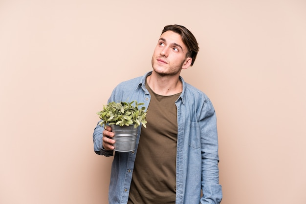 Young caucasian man holding a plant dreaming of achieving goals and purposes