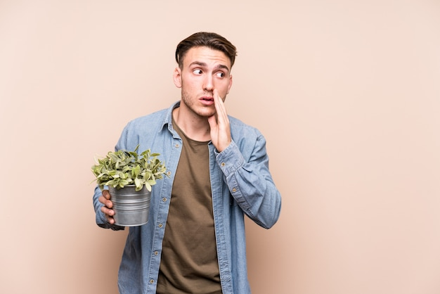 Young caucasian man holding a plant is saying a secret hot braking news and looking aside