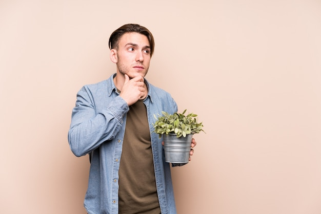 Young caucasian man holding a plant looking sideways with doubtful and skeptical expression.