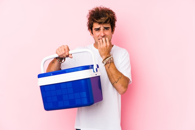 Young caucasian man holding a portable fridge biting fingernails, nervous and very anxious.