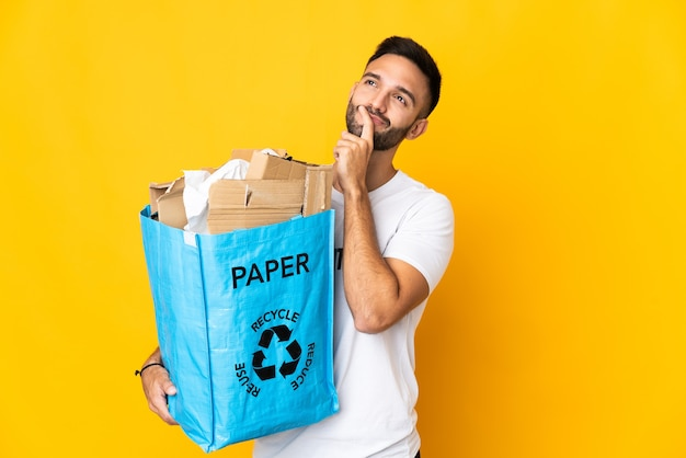 Young caucasian man holding a recycling bag full of paper to recycle isolated on white background having doubts while looking up