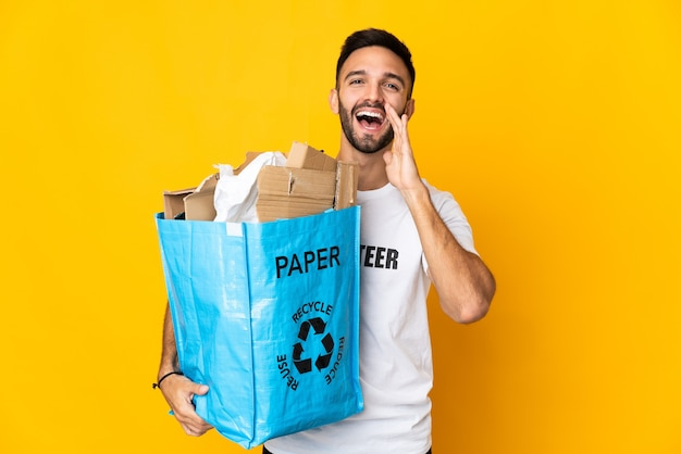 Young caucasian man holding a recycling bag full of paper to recycle isolated on white background shouting with mouth wide open