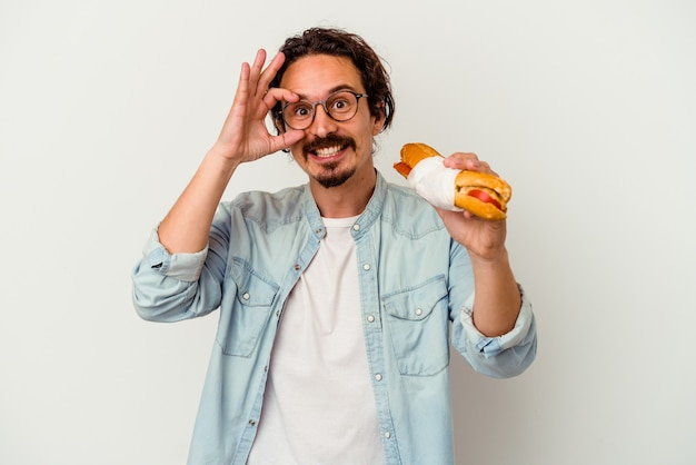 Young caucasian man holding a sandwich isolated on white wall excited keeping ok gesture on eye.