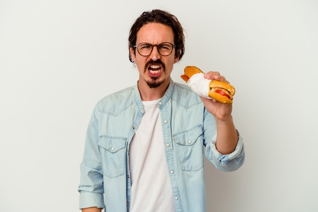 Young caucasian man holding a sandwich isolated on white wall screaming very angry and aggressive.
