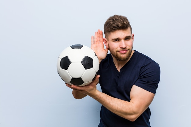 Young caucasian man holding a soccer ball trying to listening a gossip.
