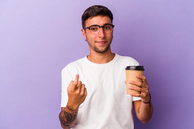 持っている若い白人男性は、招待が近づくようにあなたに指を指して紫色の背景に分離されたコーヒーをテイクアウトします。