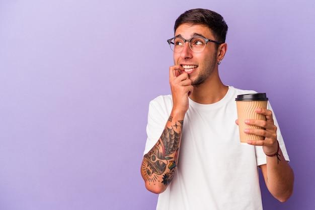 紫色の背景に分離されたコーヒーを持ち帰る白人の若い男は、コピースペースを見ている何かについて考えてリラックスしました。