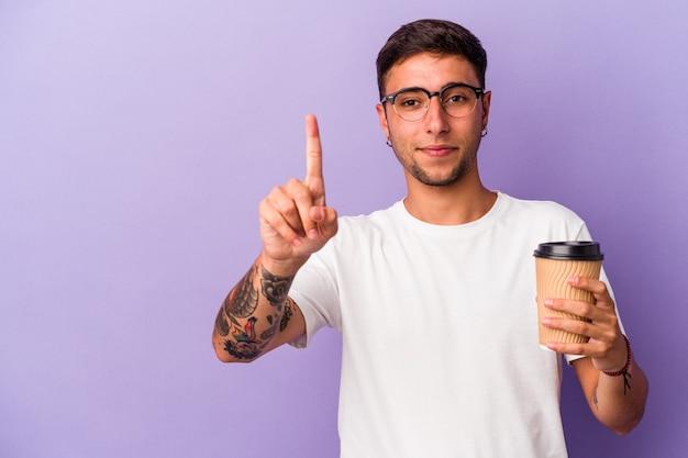 保持している若い白人男性は、指でナンバーワンを示す紫色の背景に分離されたコーヒーをテイクアウトします。