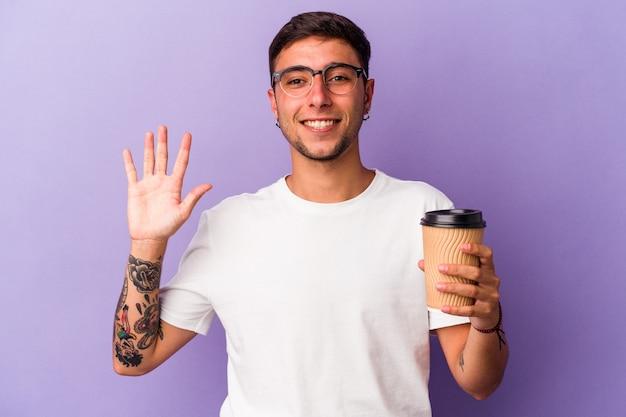 保持している若い白人男性は、指で5番を示す陽気な笑顔の紫色の背景に分離されたコーヒーをテイクアウトします。