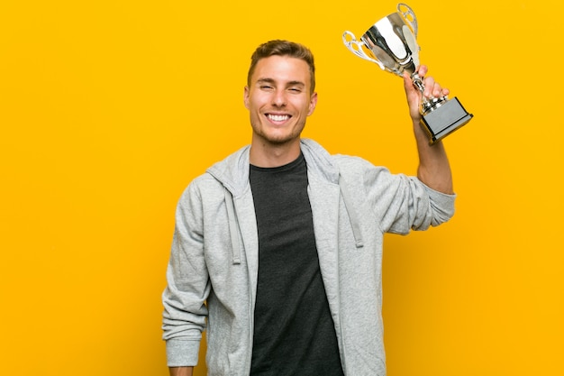 Young caucasian man holding a trophy happy, smiling and cheerful.