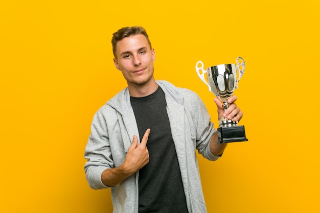Young caucasian man holding a trophy pointing with finger at you as if inviting come closer.