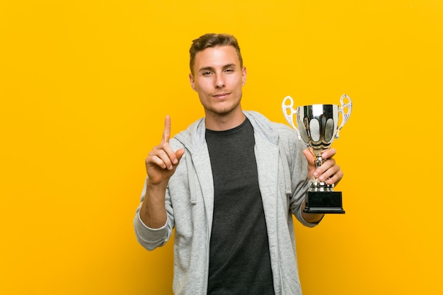 Young caucasian man holding a trophy showing number one with finger.