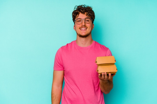 Young caucasian man holding two burgers isolated on blue background happy, smiling and cheerful.