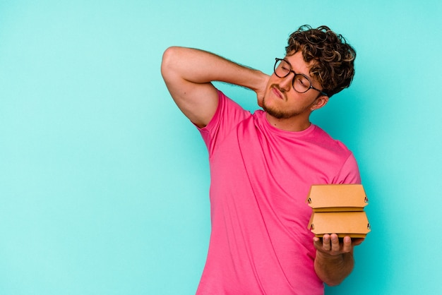 Young caucasian man holding two burgers isolated on blue background touching back of head, thinking and making a choice.
