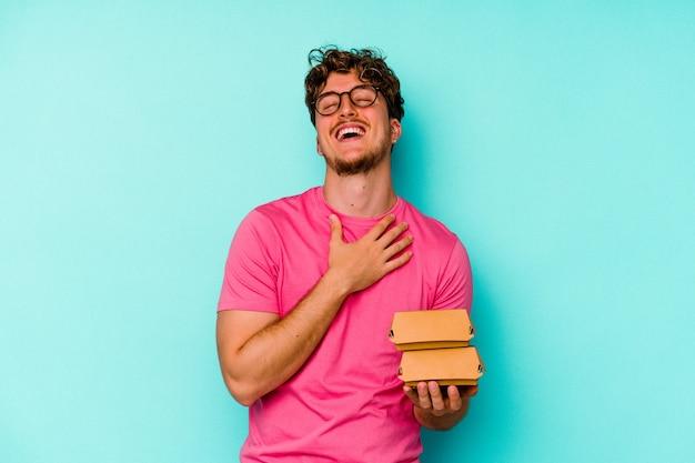 青い背景に分離された2つのハンバーガーを保持している若い白人男性は、胸に手を置いて大声で笑います。 Premium写真