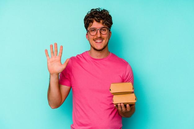 Молодой кавказский человек, держащий два гамбургера, изолированные на синем фоне, улыбается веселый, показывая номер пять с пальцами.