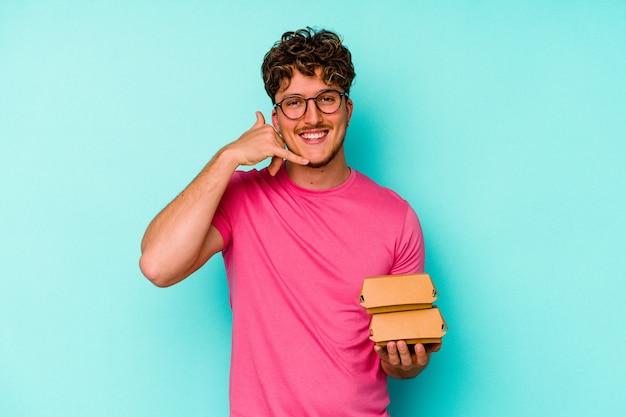 指で携帯電話の呼び出しジェスチャーを示す青い壁に分離された2つのハンバーガーを保持している若い白人男性。