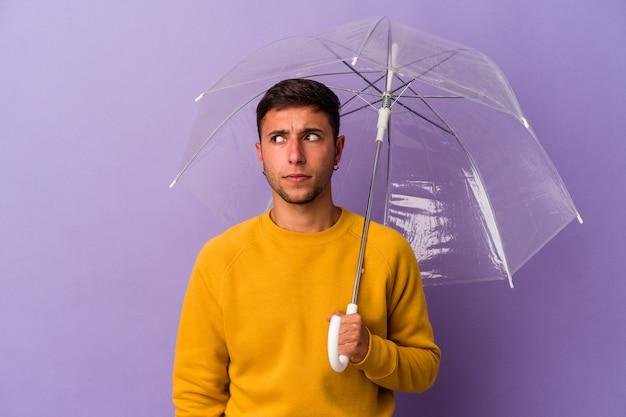 紫色の背景に孤立した傘を持っている若い白人男性は混乱し、疑わしく、不安を感じています。
