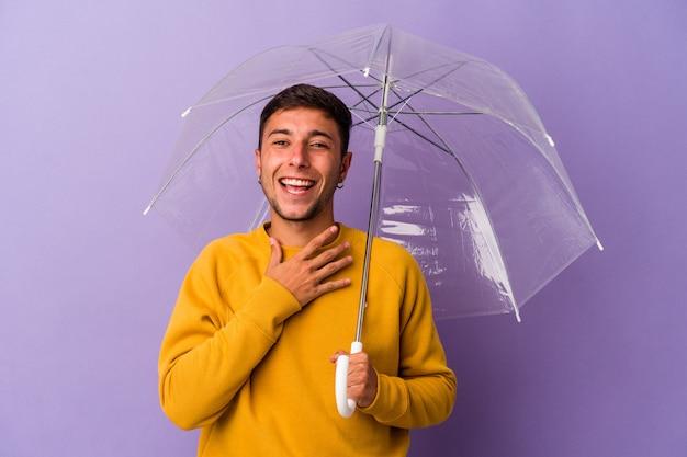 紫色の背景に孤立した傘を持っている若い白人男性は、胸に手を置いて大声で笑います。