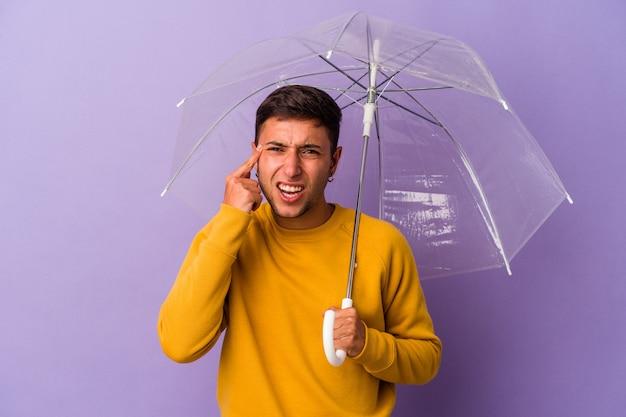 人差し指で失望のジェスチャーを示す紫色の背景に孤立した傘を保持している若い白人男性。