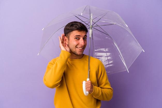 ゴシップを聴こうとしている紫色の背景に孤立した傘を持っている若い白人男性。