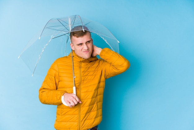 Young caucasian man holding an umbrella touching back of head, thinking and making a choice.