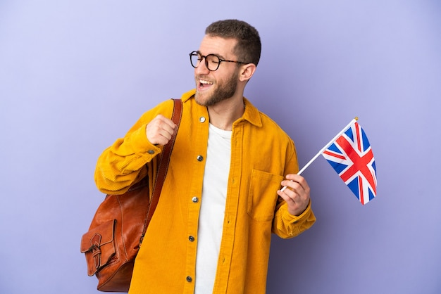 Young caucasian man holding an united kingdom flag isolated on purple background celebrating a victory