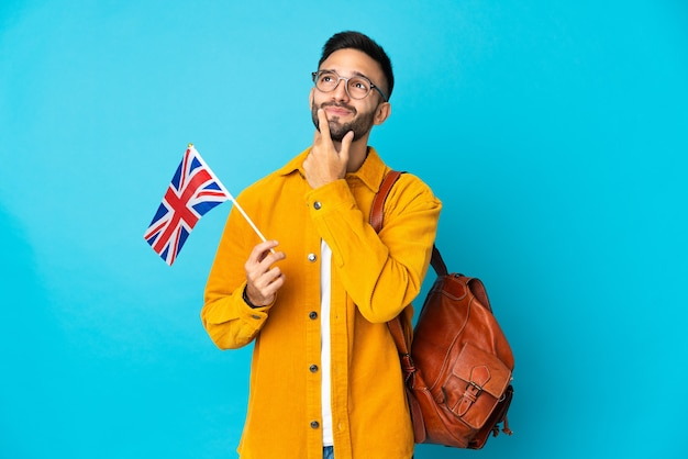 Young caucasian man holding an united kingdom flag isolated on yellow background having doubts while looking up