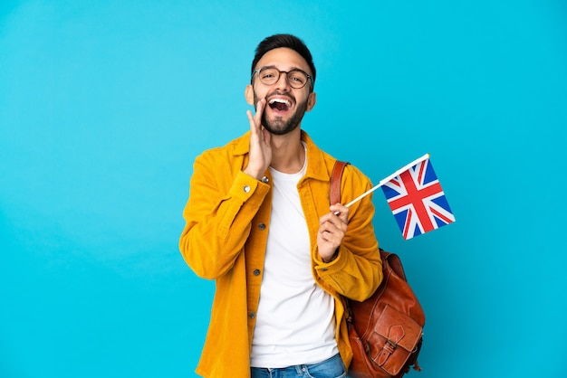 Young caucasian man holding an united kingdom flag isolated on yellow background shouting with mouth wide open