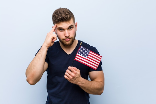 Young caucasian man holding a united states flag pointing his temple with finger, thinking, focused on a task.