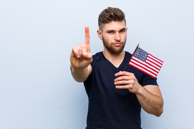 Young caucasian man holding a united states flag showing number one with finger.