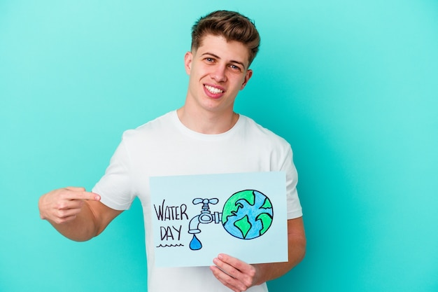 Young caucasian man holding a water day placard isolated on blue