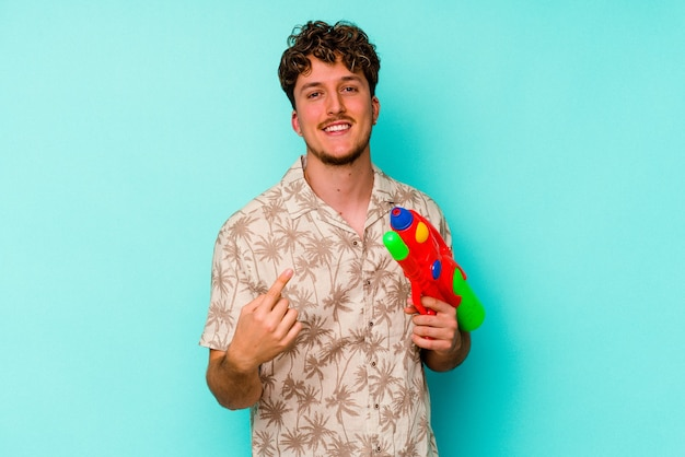 Young caucasian man holding a water gun isolated on blue background pointing with finger at you as if inviting come closer.