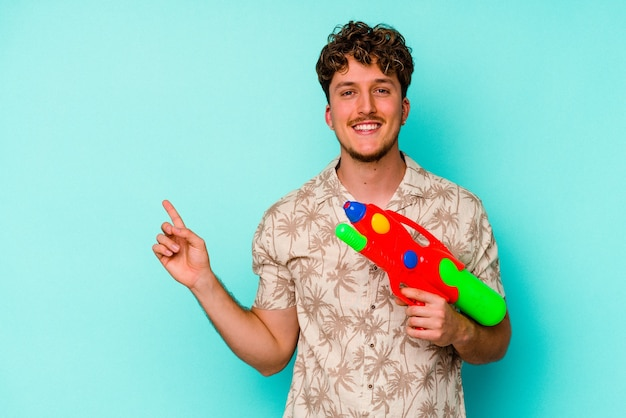 Young caucasian man holding a water gun isolated on blue background smiling and pointing aside, showing something at blank space.