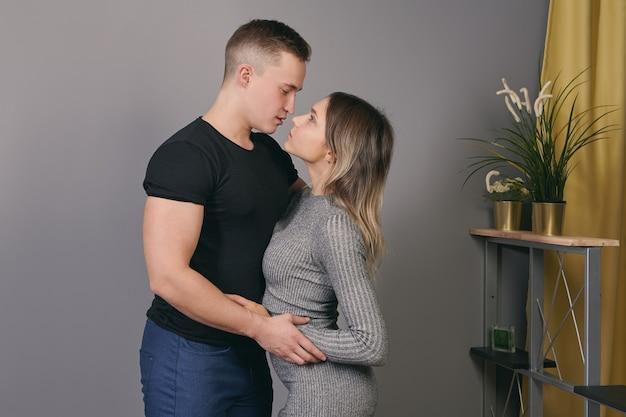Молодой кавказский мужчина обнимает белую женщину в помещении.