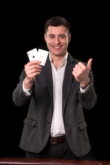 검은 양복과 흰색 셔츠를 입은 백인 청년이 손에 두 개의 에이스를 들고 검은색 바탕에 미소를 지으며 엄지손가락을 치켜들고 있습니다. 도박 개념입니다. 카지노