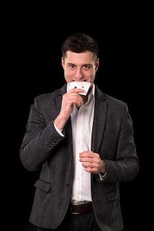 暗いスーツと黒い背景に彼の手と歯に2つのエースを保持している白いシャツを着た若い白人男性。ギャンブルの概念。カジノ