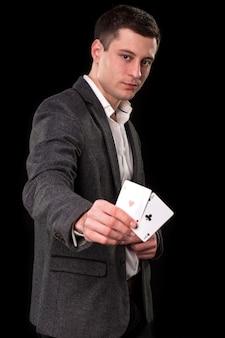 黒の背景に彼の手で2つのエースを保持している暗いスーツと白いシャツを着た若い白人男性。ギャンブルの概念。カジノ