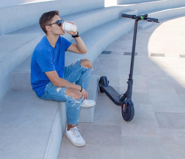 電動スクーターの近くの石の階段に屋外で座って、コーヒーを飲みながら青いtシャツを着た若い白人男性。電気自動車のコンセプト
