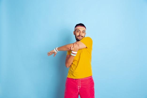 青い背景の明るい服のトレーニングで若い白人男性スポーツ、人間の感情、顔の表情、健康的なライフスタイル、若者、販売の概念。ストレッチ体操をする。コピースペース。