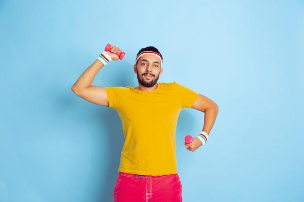 Молодой кавказский человек в яркой одежде, тренирующийся на синем пространстве, концепция спорта, человеческие эмоции, выражение лица, здоровый образ жизни, молодежь, продажи