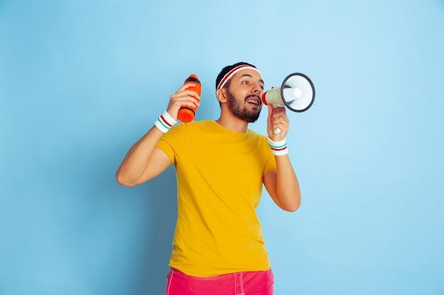 青い空間で明るい服のトレーニングをしている若い白人男性スポーツ、人間の感情、表情、健康的なライフスタイル、若者、販売の概念