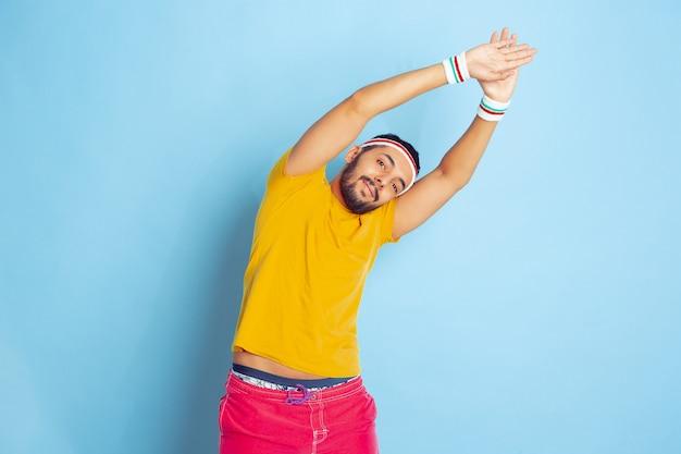 青い空間の明るい服のトレーニングで若い白人男性スポーツ、人間の感情、顔の表情、健康的なライフスタイル、若者、販売の概念