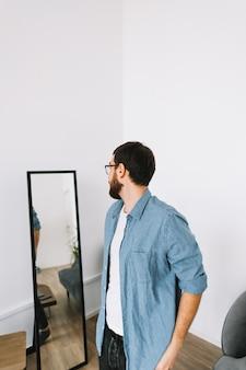 거실에서 거울에 서 안경에 젊은 백인 남자.